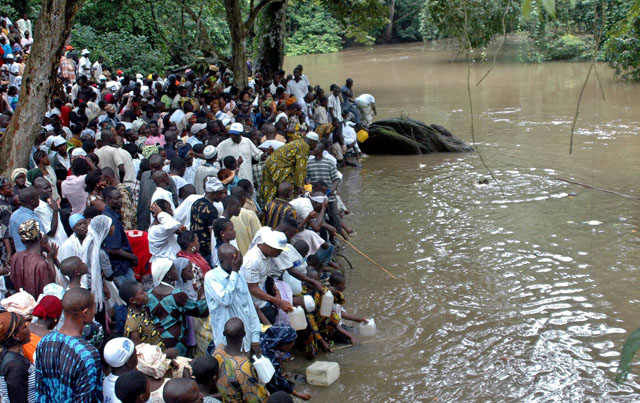 People gather at the Osun sacred river to collect water during the annual worship festival of a river goddess in Osogbo